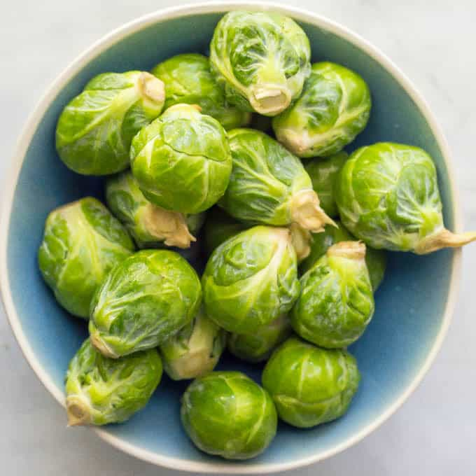 Whole raw Brussels sprouts in a round blue bowl