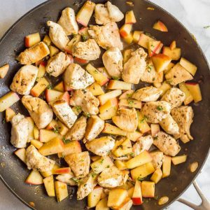 Sautéed chicken and apples in pan with rosemary