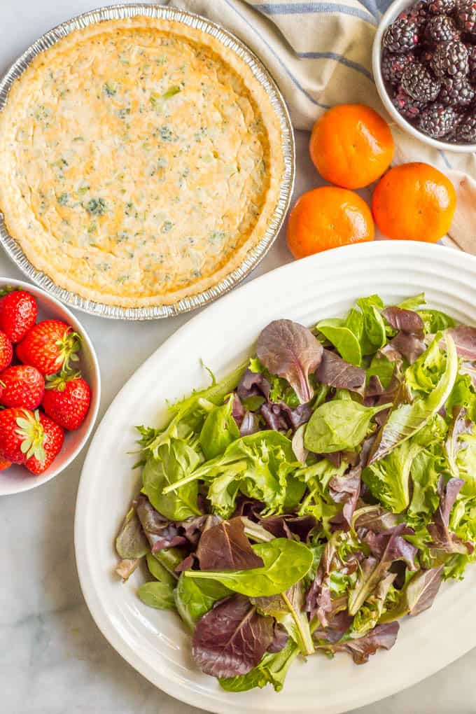 Mixed greens salad with fruit ingredients arranged with a quiche