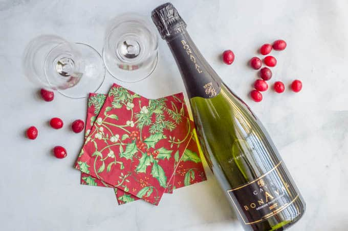 Bottle of Cava Brut sparkling wine with cranberries, napkins and champagne glasses