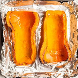 Roasted butternut squash on a sheet pan with middles scooped out