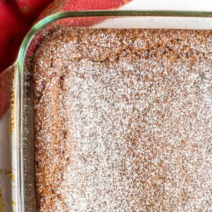Close up of whole wheat gingerbread bars in pan with powdered sugar dusted on top