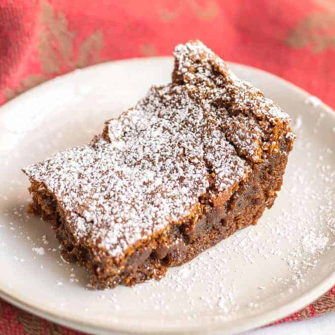 A single whole wheat gingerbread bar with powdered sugar on a white plate