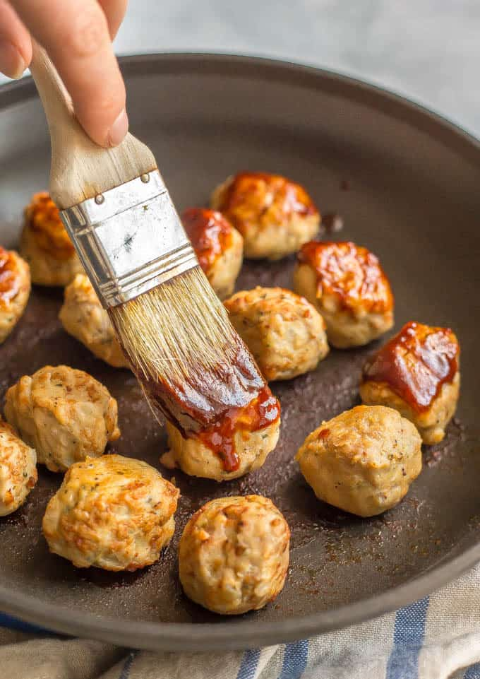 Chicken meatballs in a pan being basted with a BBQ sauce glaze
