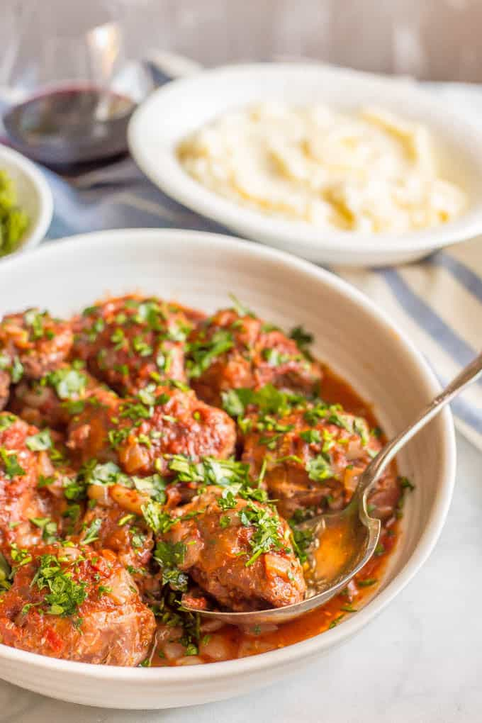 Slow cooker bistro chicken thighs are easy to prep and cook all day in a delicious, rich red wine and tomato sauce. Serve over mashed potatoes, rice or pasta for a yummy dinner! #slowcooker #chickendinner #slowcookerchicken | www.familyfoodonthetable