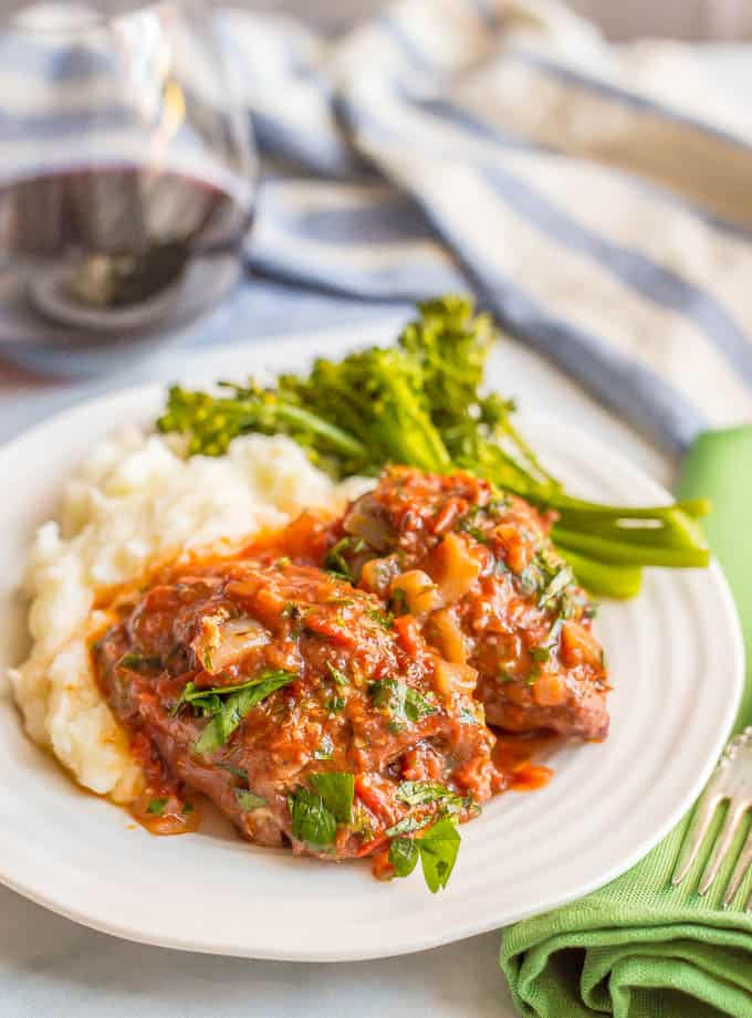 Slow cooker bistro chicken thighs served over mashed potatoes with broccolini and a glass of red wine in the background