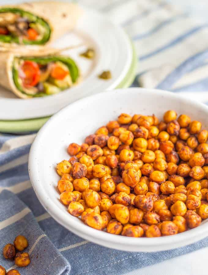 Crunchy BBQ roasted chickpeas in a white bowl with a blue striped towel underneath and a veggie wrap on a plate in the background