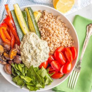 Overhead shot of farro and roasted vegetable grain bowl with spinach and kale dip and a green napkin with a fork on the side