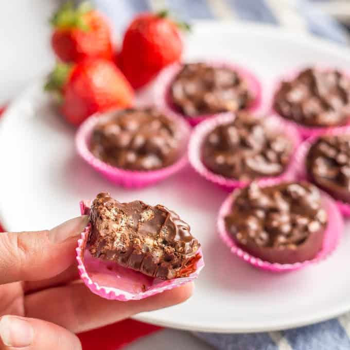 3 ingredient homemade crunch cup with a pink wrapper being held with a bite taken out and more on a plate in the background
