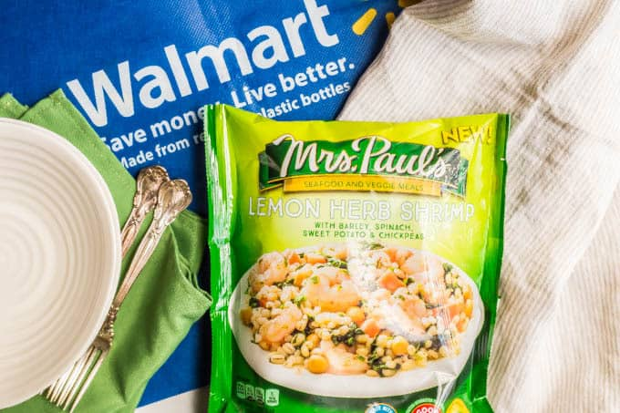 Bag of Mrs. Paul's lemon herb shrimp and veggies with a Walmart bag underneath and two bowls with napkins and forks to the left