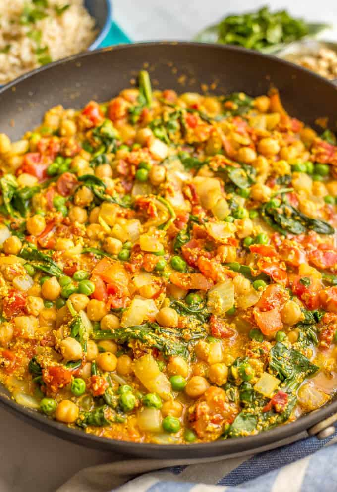 This quick and easy vegetarian curry is loaded with chickpeas, spinach, green peas and plenty of warm spices for a bright, beautiful and flavorful dinner! #curryrecipe #vegetariancurry #easyvegetarian #quickeasydinner | www.familyfoodonthetable.com