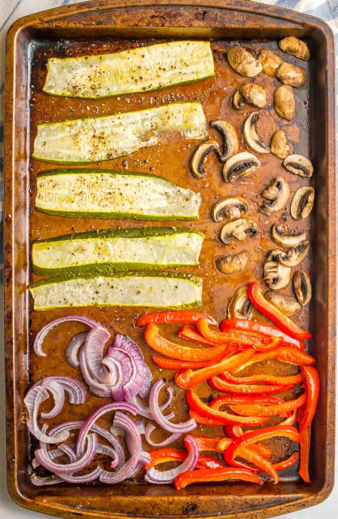 Sheet pan of roasted veggies including zucchini, mushrooms, red bell pepper and red onions