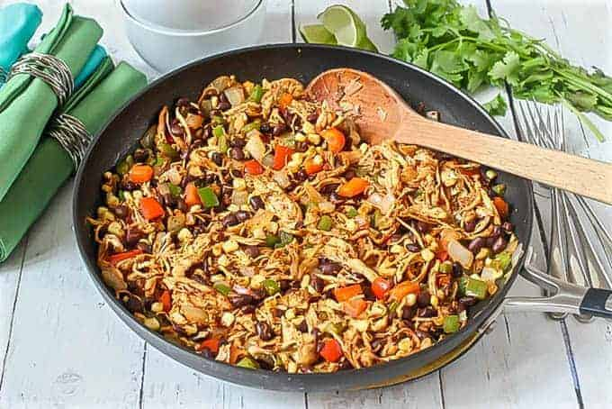 Southwest chicken skillet dinner prepared in pan with a wooden spoon