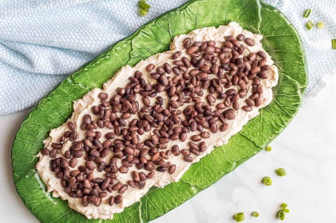 7-layer Mexican cream cheese dip being assembled on a green serving plate with cream cheese layer and black beans