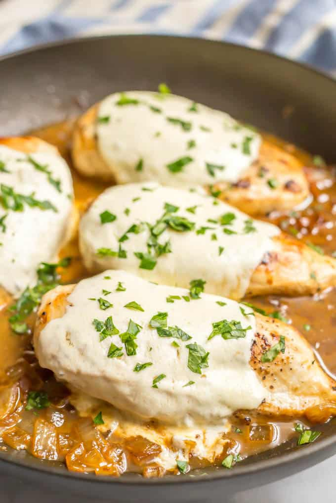 Side angle shot of easy mozzarella baked chicken breasts with melted mozzarella cheese and a sprinkling of parsley in a saute pan