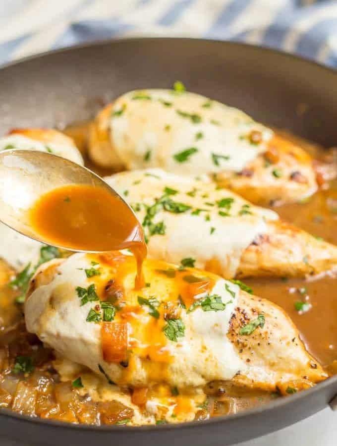 A spoonful of sauce being poured over easy mozzarella baked chicken breast in a saute pan