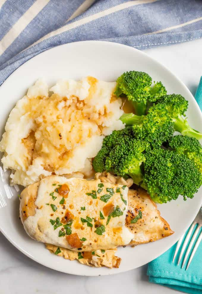 Plated dinner of easy mozzarella baked chicken, mashed potatoes and steamed broccoli on a white plate with a fork to the side