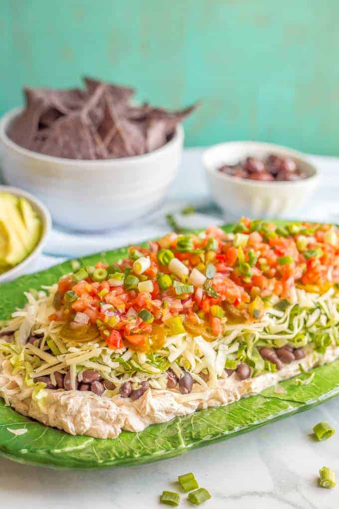 Side angle styled photo of healthy 7-layer Mexican dip on a green serving platter with bowls of chips, avocado and olives in the background and a sprinkling of green onions