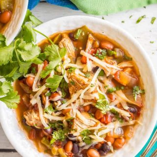 Overhead close-up shot of healthy slow cooker chicken chili served in a white bowl with shredded cheese and cilantro on top and a spoon on a turquoise napkin nearby