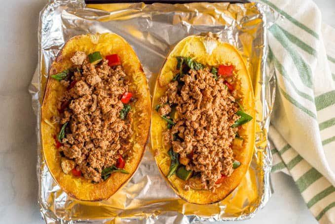 A roasted spaghetti squash cut in half and stuffed with veggies and ground turkey on a baking tray lined with foil and a green striped towel in the background