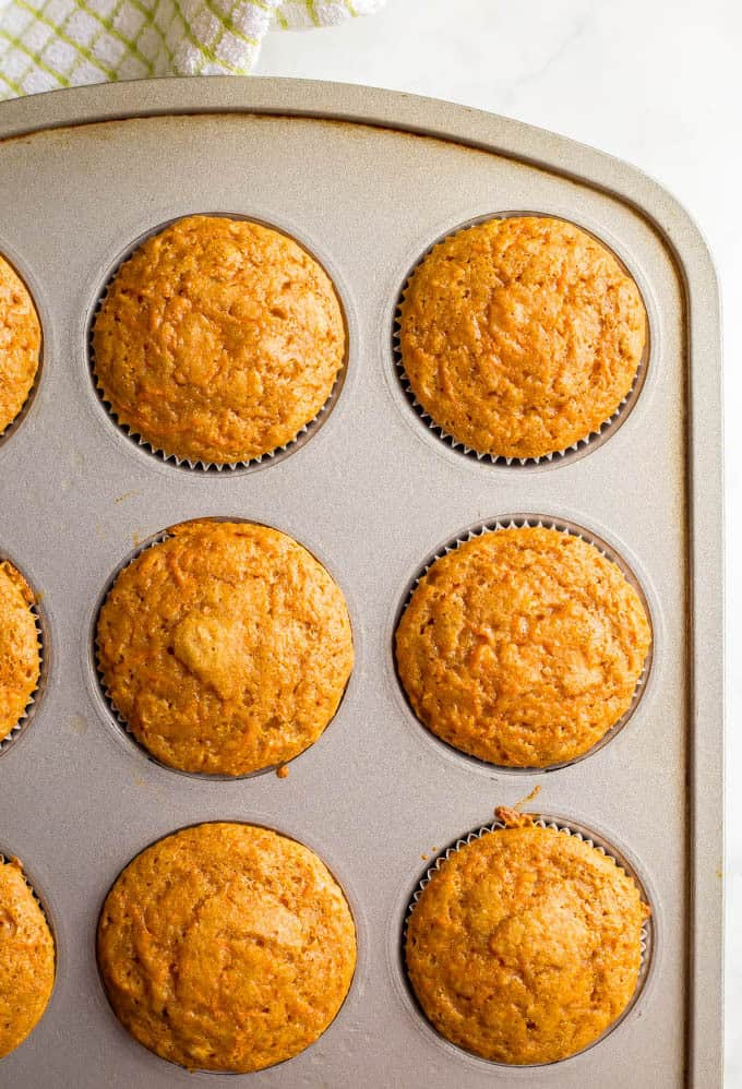 Overhead close-up photo of baked whole wheat carrot cake muffins in muffin tin