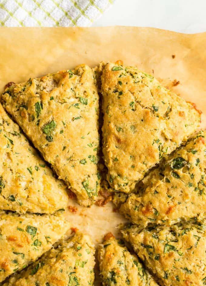 Close up of whole wheat spinach cheddar scones after being baked on a parchment sheet with a green towel