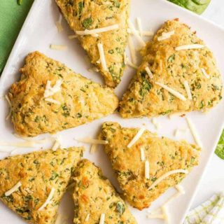 6 whole wheat spinach cheddar scones arranged on a white serving tray with a green towel nearby and a sprinkling of spinach leaves and shredded cheddar cheese