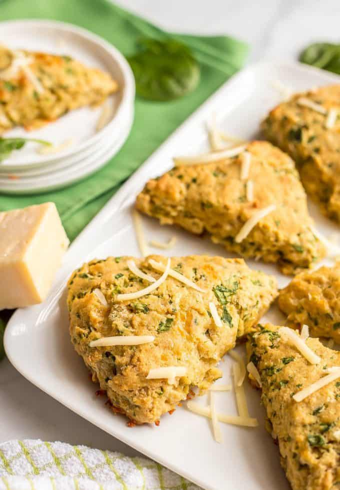 Side angle of whole wheat spinach cheddar scones arranged on a white serving tray with a green towel nearby and a sprinkling of spinach leaves and shredded cheddar cheese and a white serving plate with a scone in the background