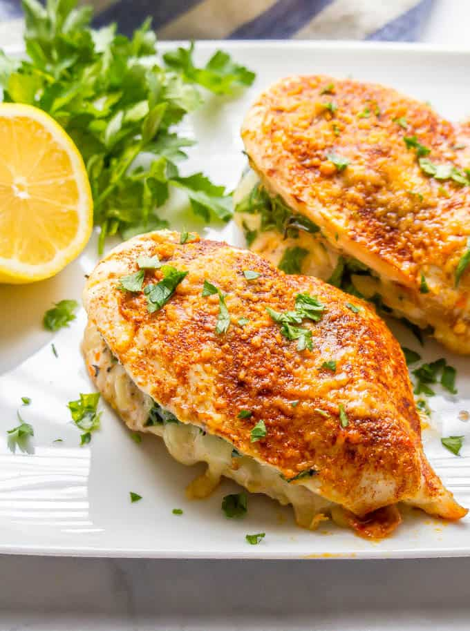 Top-down photo of chicken breasts stuffed with prosciutto, spinach and mozzarella cheese sprinkled with parsley with parsley and a cut lemon on the side of the plate