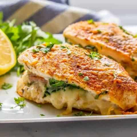 Close-up photo of chicken breasts stuffed with prosciutto, spinach and mozzarella cheese sprinkled with parsley