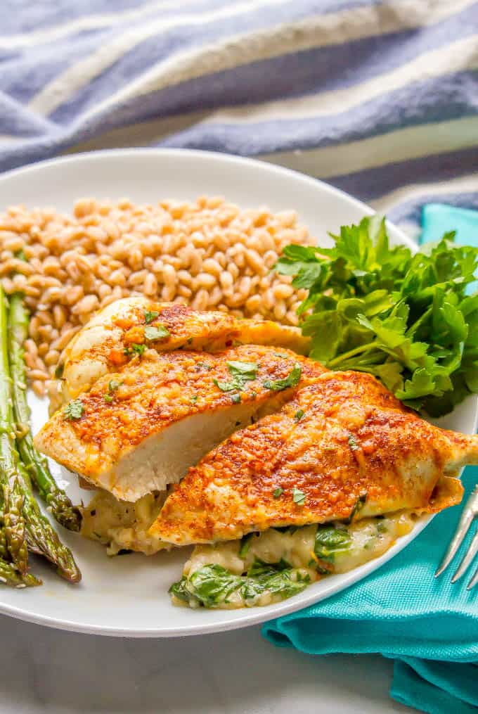 A dinner plate with chicken stuffed with prosciutto, spinach and mozzarella cheese and sides of cooked farro and steamed asparagus