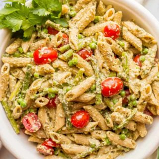 This warm and creamy pesto pasta with spring vegetables is an easy one-pot pasta recipe with peas, asparagus, and ricotta and Parmesan cheeses. It's great as a light vegetarian meal or as a side dish at dinner! #pestopasta #vegetarianpasta #springpasta | www.familyfoodonthetable.com