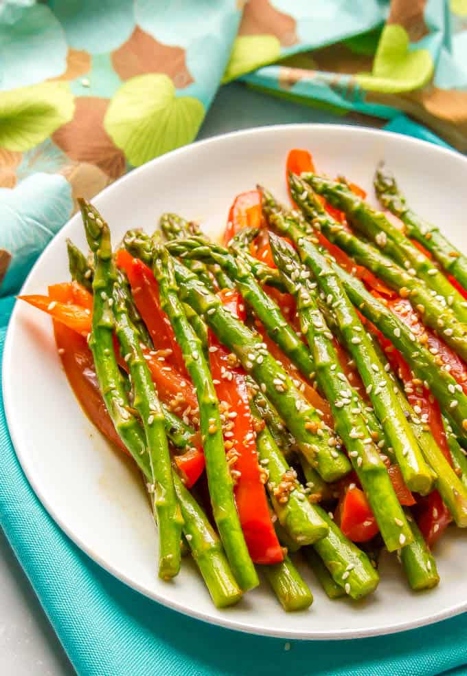 Side angle of sauteed sesame asparagus and red bell peppers on a white plate with colorful napkins in the background