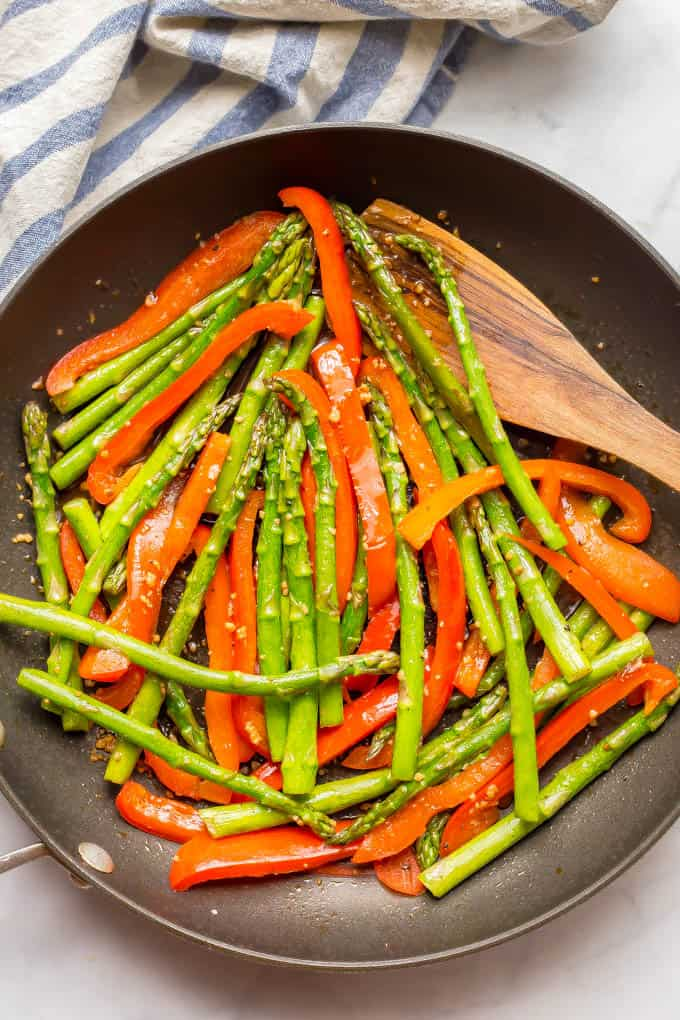Sesame asparagus and red peppers in a saute pan with a wooden spoon