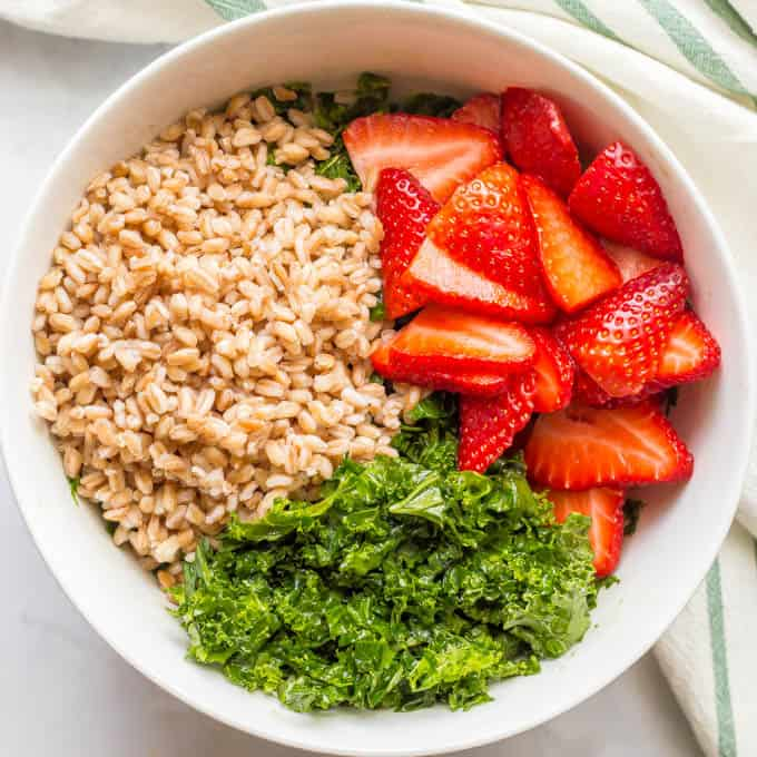 Farro, kale and strawberry salad ingredients separated in a white bowl