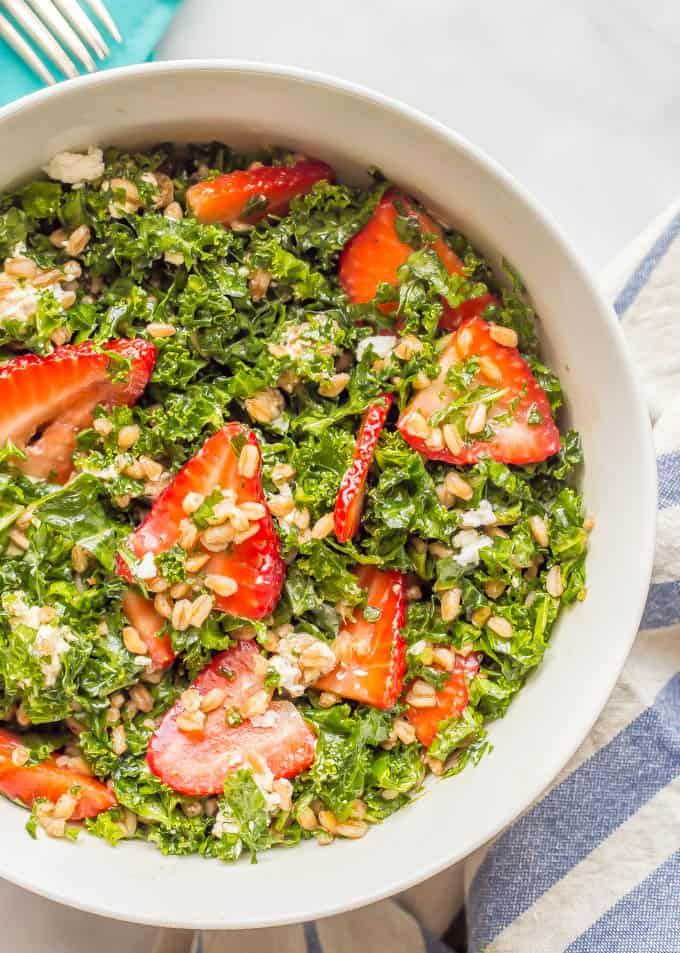 Overhead close-up shot of farro kale and strawberry salad with goat cheese in a white bowl