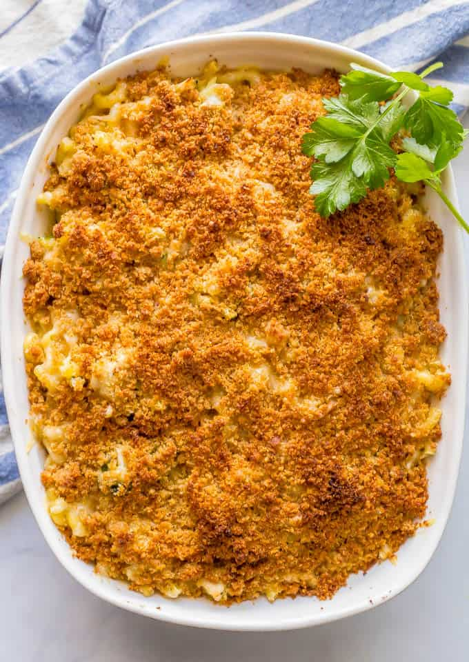 Overhead shot of baked healthy chicken broccoli mac and cheese casserole with a buttery breadcrumb topping and a blue striped towel nearby