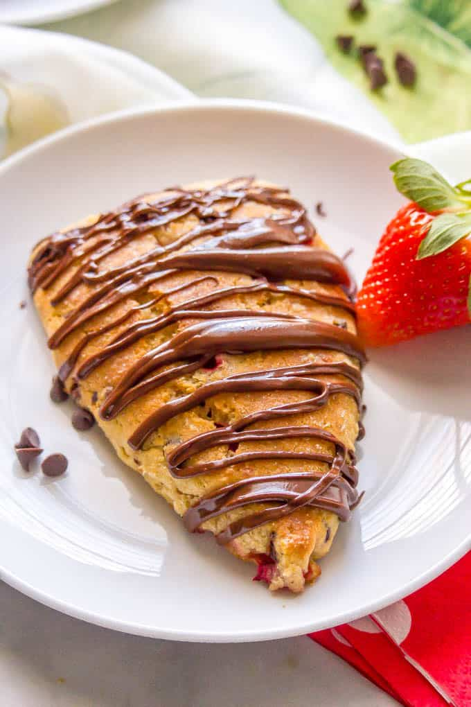 Close-up of a Nutella-drizzled healthy strawberry scone on a white serving plate