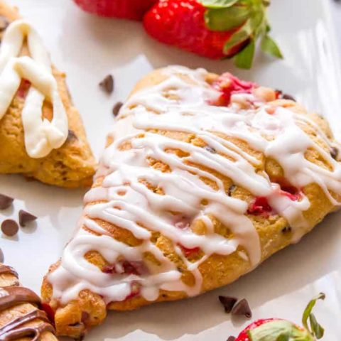 Close-up of a healthy strawberry scone with a lemon glaze drizzled on top and fresh strawberries to the side