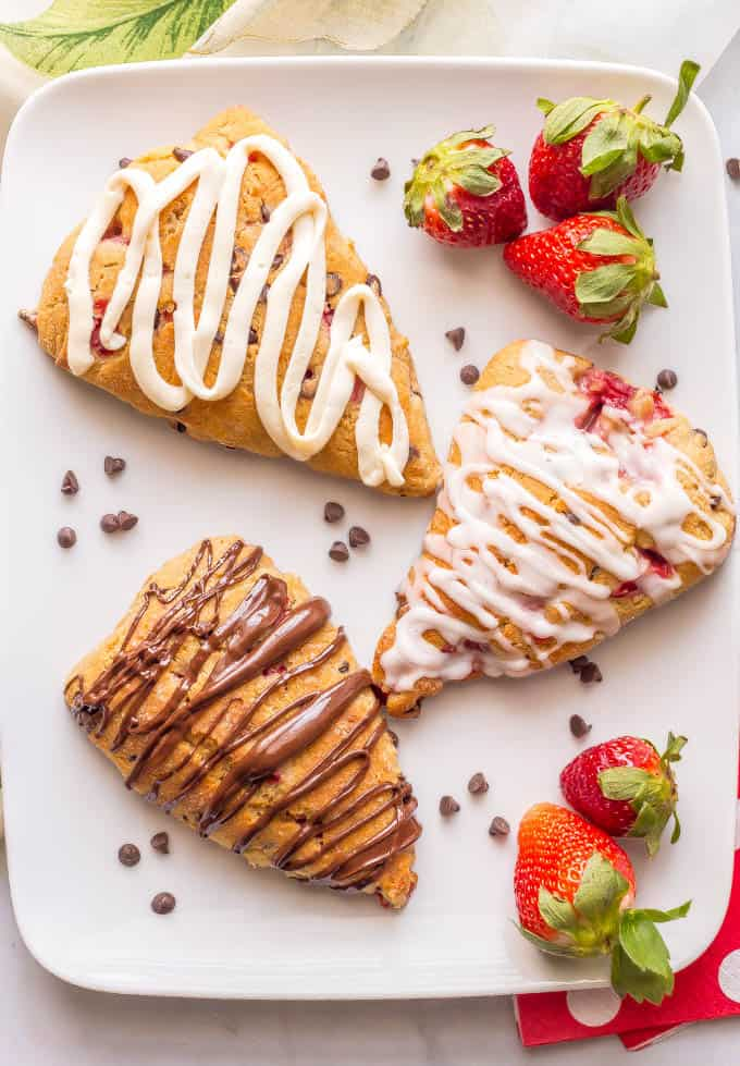 Healthy strawberry scones on a platter with mini chocolate chips, fresh strawberries and a variety of frostings and glazes drizzled on top