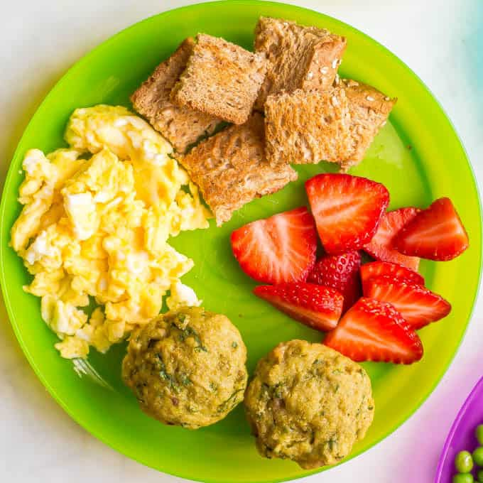 Green kids plate with scrambled eggs, toast pieces, strawberries and mini spinach banana muffins