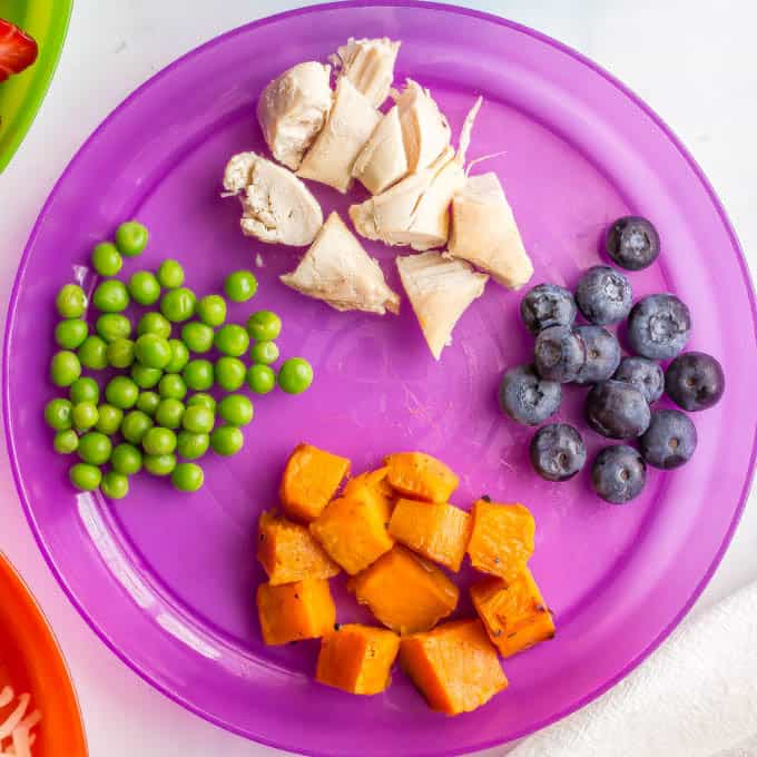 Purple kids plate with peas, chicken, blueberries and sweet potato