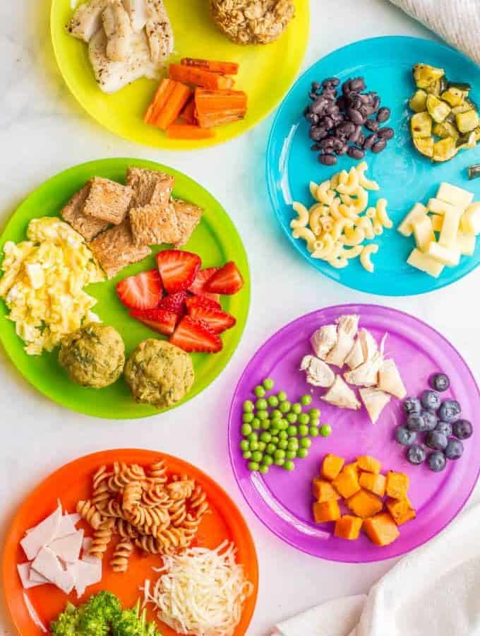 Overhead image of colorful plates with a variety of healthy baby finger foods and toddler finger foods