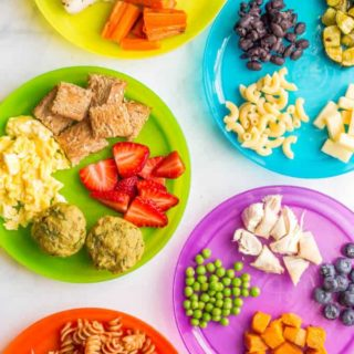 Colorful kid plates with an array of finger food options