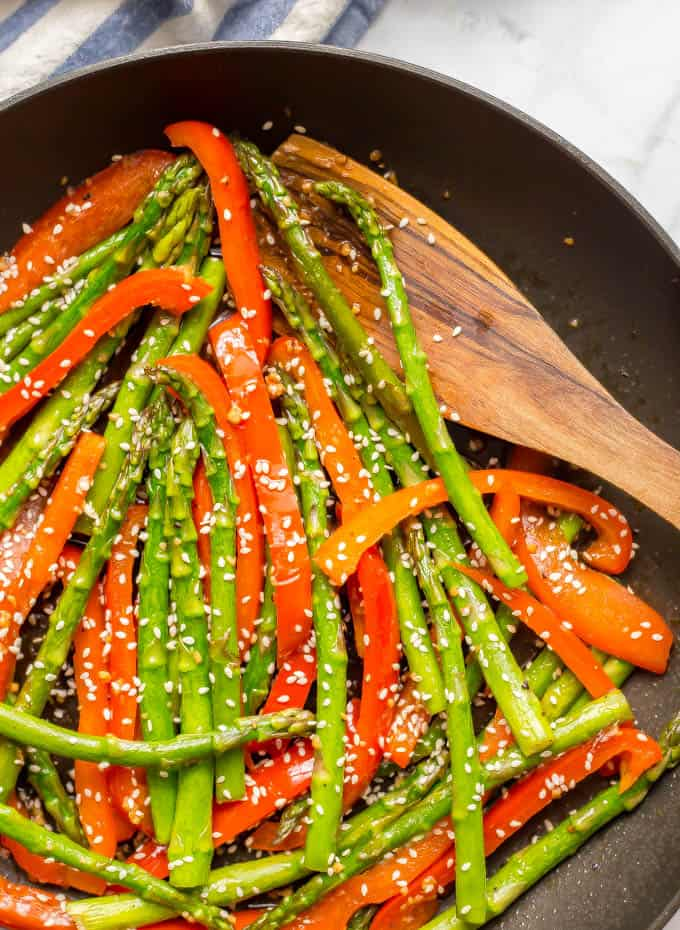 Close- up of sesame asparagus and red peppers in a saute pan with a wooden spoon and a sprinkling of sesame seeds