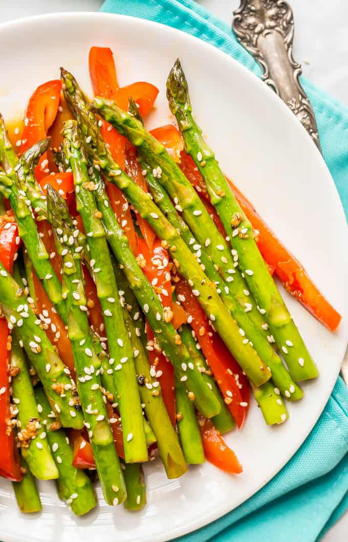 Close-up of sesame asparagus and red peppers on a round white plate with a napkin and serving fork in the background
