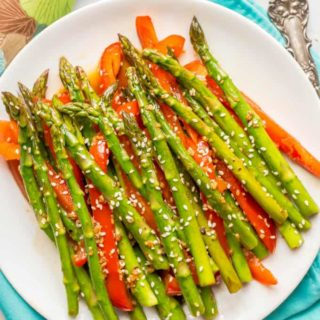 Sesame asparagus and red peppers on a round white plate with napkins in the background