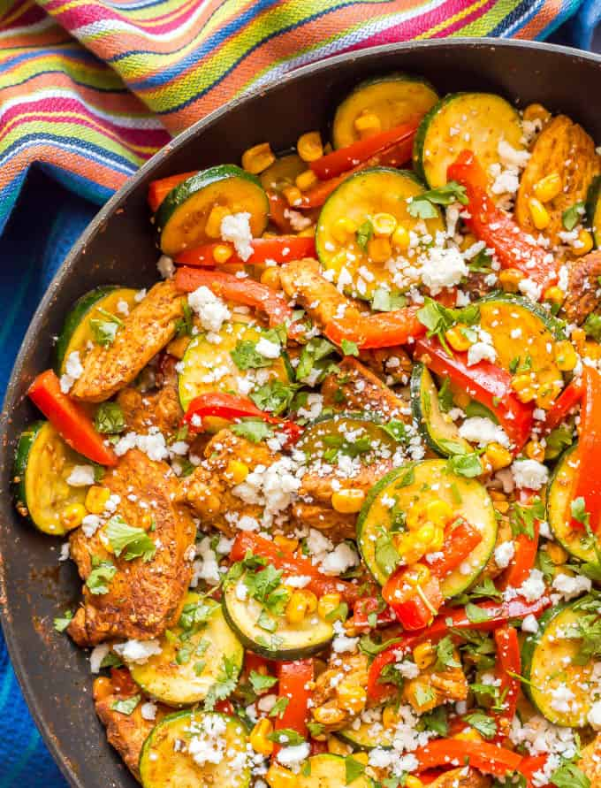 Close-up of healthy chicken and zucchini skillet with corn and peppers in a pan with a striped towel underneath