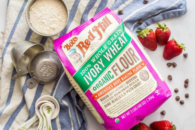 Bob's Red Mill Ivory Wheat flour in a bag with measuring cups, strawberries and chocolate chips nearby