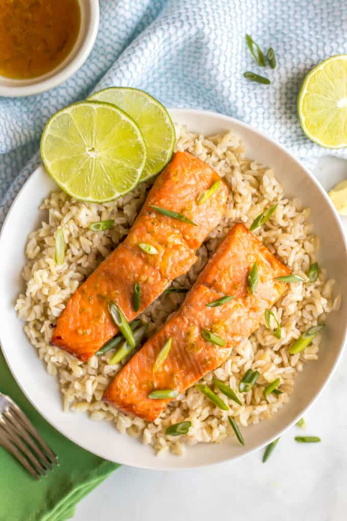 Honey lime roasted salmon on a bed of brown rice with scallions and lime slices